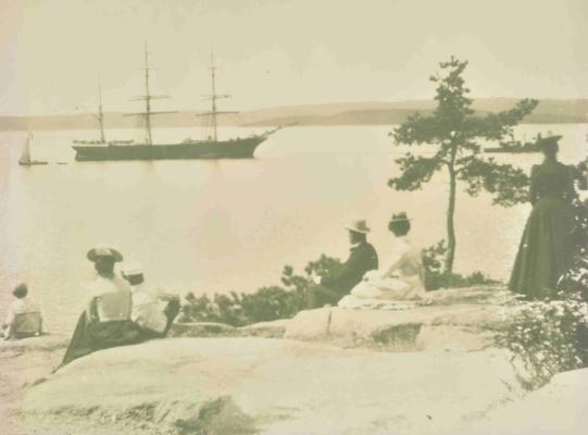 Fotoet av den flotte seilskuten under slep og sommergjester i fasjonable og tidsriktige antrekk, er fra 1901 og er tatt fra omtrent der tåkeklokken ble bygget to år senere (utlånt av Tor Bjørnstad)