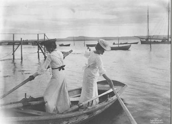 Kate og Agathe i robåt ved Sundestranda, den gamle badebryggen i bakgrunnen (Wilse, 1904)