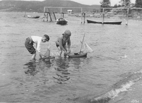 Gutter leker med seilbåter på Sundestranda, badebryggen i bakgrunnen, lengre bak et gammelt badehus (Wilse, 1904)