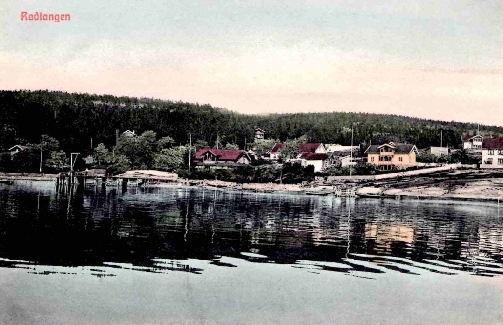 Håndkolorert foto fra cirka 1906, som viser deler av gamle Rødtangen sentrum sett fra fjorden. Hotellet er nyrenovert og utvidet med blant annet stor glassveranda.