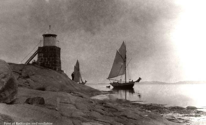 Fyret på Rødtangen med sandjakter. Foto: Thorleif Thoresen. Årstall ukjent. Fra slutten av 1800-tallet til langt innpå 1900-tallet fraktet flere hundre sandjakter sand fra morenene på begge sider av Svelvikstrømmen til kunder mest langs Oslofjorden.