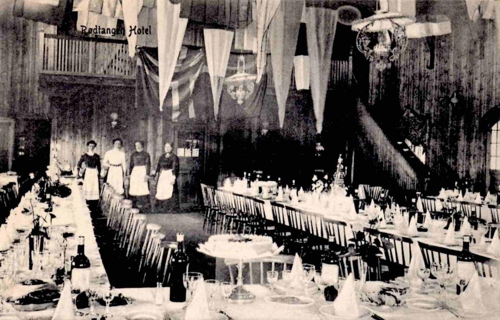 Salen i Rødtangen Hotel på jordet ble brukt både til matserving og dans. Her er salen dekket til festmiddag, med betjeningen i bakgrunnen.
