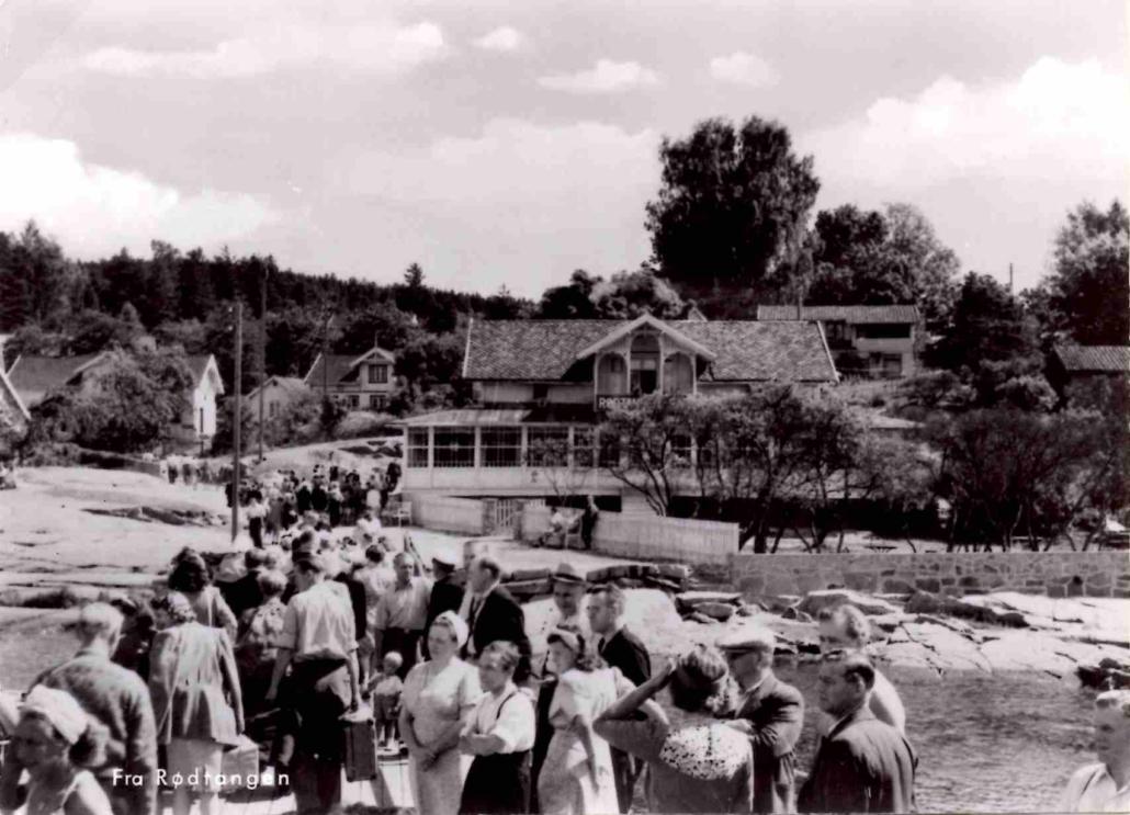 """«Fra Rødtangen». Fotoet er fra 1950-tallet, og rutebåtene er fortsatt viktigste transportmiddel til og fra Rødtangen. På 1950-tallet var Rødtangen Bad blant annet Norsk Folkehjelps feriested for slitne husmødre, og på folkemunnet kalte noen det for """"tynnslitten"""" - badet var også nokså nedslitt. Utgiver: K. Harstad Kunstforlag."""
